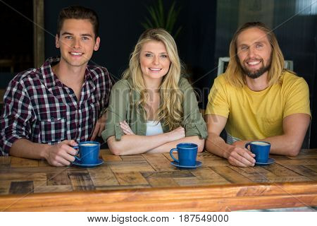 Portrait of happy friends having coffee at wooden table in cafe