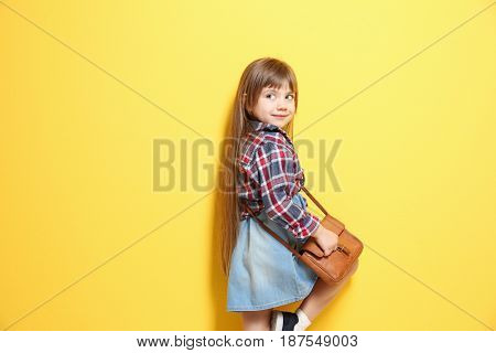 Cute little girl on color background. Fashion concept