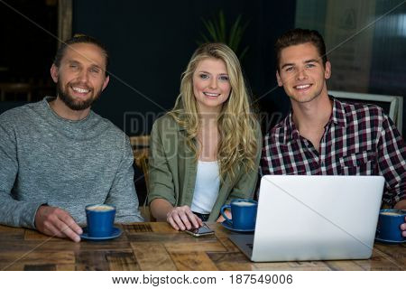 Portrait of happy friends having coffee at table in cafeteria