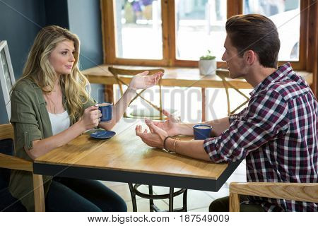 Young couple talking while having coffee at table in cafe