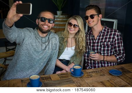Happy man with friends taking selfie at table in coffee shop