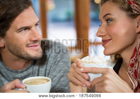 Close-up of romantic young couple having coffee in cafeteria