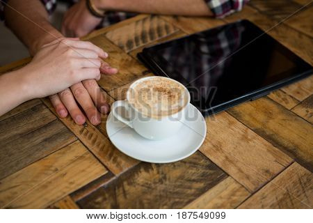 Cropped image of couple holding hands with coffee cup and tablet PC on table in cafe