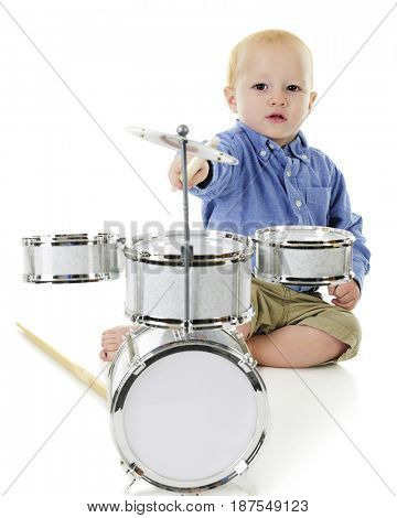 An adorable toddler boy stretching for the cymbal on his tiny drum set.  On a white background.