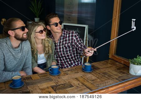 Happy friends taking selfie with monopod at table in cafeteria