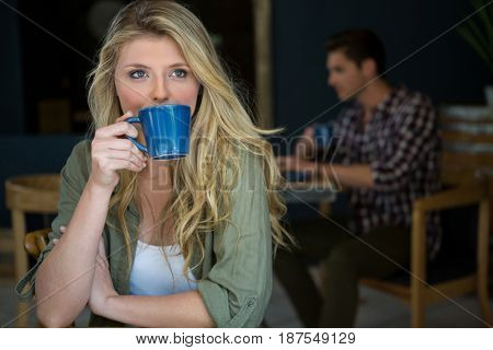 Young woman drinking coffee with man sitting in background at cafeteria