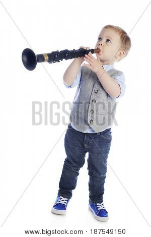 Full length image of an adorable preschooler looking up as he plays a toy clarinet.  On a white background.