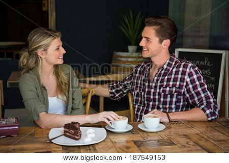 Loving young couple talking at table in coffee shop