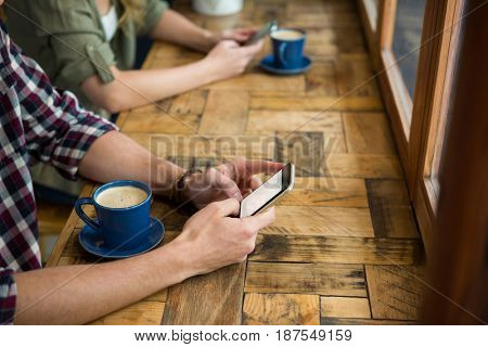 Cropped image of man and woman using mobile phones in coffee shop