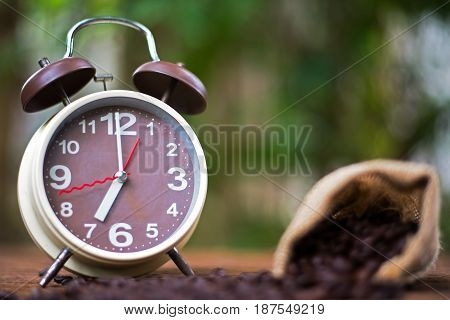 Alarm clock with coffee beans on wooden table with morning light Start up concept select fucus clock