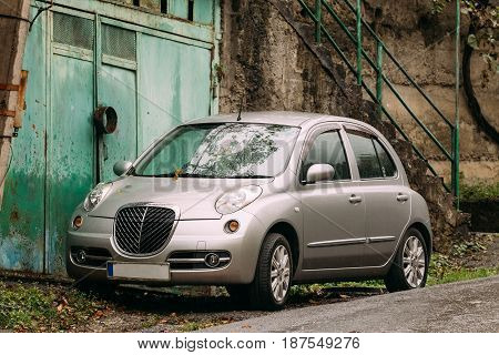 Borjomi, Georgia - October 25, 2016: Nissan March Bolero parked near village house at rainy autumn day. The Micra is a supermini produced by the Japanese manufacturer Nissan since 1982