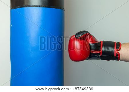 Pugilist Wearing Red And Black Boxing Gloves Starting To Punch Straight On A Blue Punching Bag
