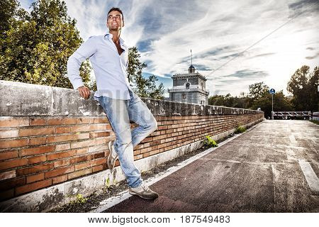 Handsome smiling man outdoors. Tiber river from the bridge. A beautiful young Italian man posing outdoors on Milvian Bridge in the historic center of Rome, Italy. Blue shirt and jeans.