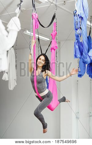 Athletic girl in grey suit practicing anti-gravity yoga jump in air using pink hammock. Mental and physical health harmony, sport activity in gym or studio