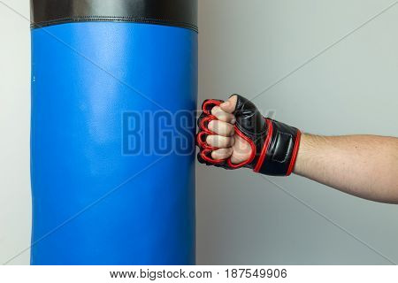 Mma Fighter Wearing Red And Black Mix Martial Arts Open Fingers Gloves Punching Straight On A Blue P