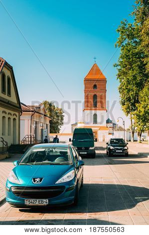 Mir, Belarus - September 2, 2016:  Peugeot Car Parking Near Saint Nicolas Roman Catholic Church In Mir, Belarus. Famous Landmark In Sunny Summer Day With Blue Sky