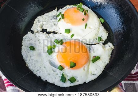 Fried eggs with green onion in black pan close up view.