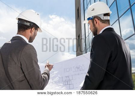 Back View Of Professional Architects In Hardhats Working With Blueprint