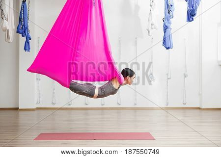 Adult woman practices anti-gravity yoga position in gym. Aerial antigravity yoga girl on pink silk hammock, doing exercises, meditating in calm position of relaxed flying body