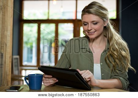 Beautiful young woman using digital tablet in cafe