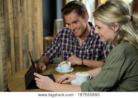Smiling young couple using digital tablet at table in coffee shop