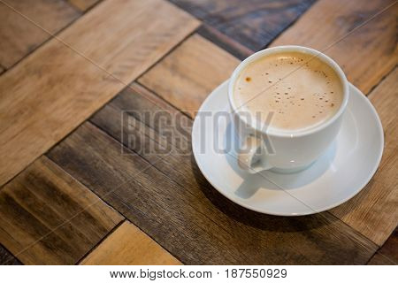 Close-up of coffee cup on wooden table in cafeteria