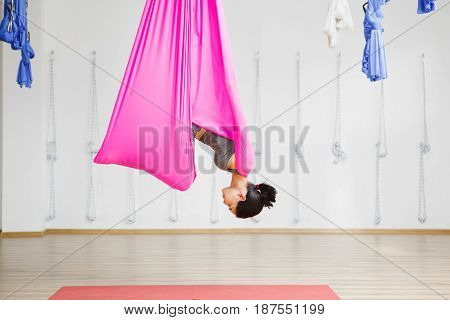 Aero yoga trainer does exercises full length. Girl hanging in hammock in upside down inversion pose. Antigravity yoga training in well lighted gym studio.