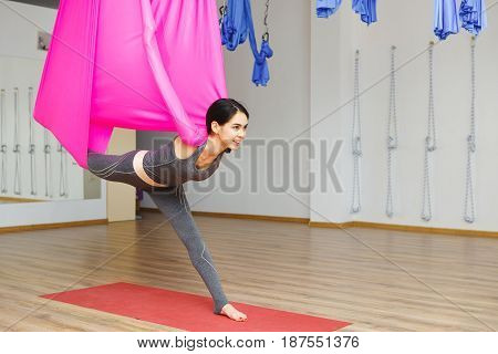 Girl stretching leg with help of hammock. Aerial exercise or antigravity yoga indoors, woman does aero poses with head leaned to back