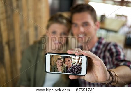 Smiling young couple taking selfie with cellphone in cafeteria