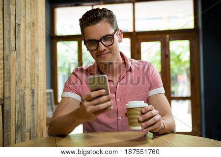 Smiling young man using mobile phone at table in coffee shop