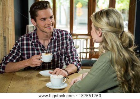 Young man having coffee while talking with woman in cafe