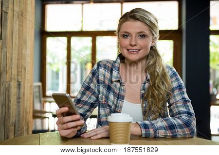 Portrait of beautiful young woman using mobile phone in cafe