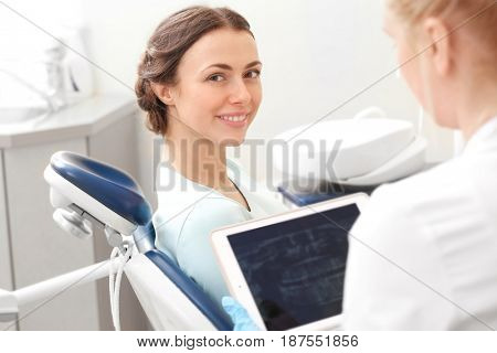 Dentist looking at X-ray image of young woman's teeth