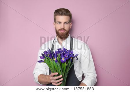 Young handsome florist with beautiful bouquet on pink background