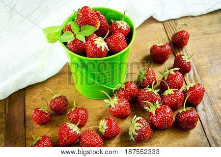 Sweet strawberries in green bucket on the kitchen table
