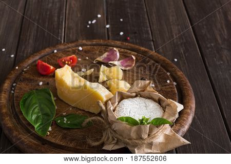 Cheese delikatessen platter on rustic wood. Wooden desk with parmesan, camembert and brie cuts decorated with garlic, tomato and basil