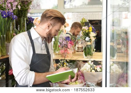 Young handsome florist writing in notebook at flower shop