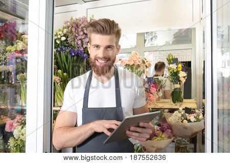 Young handsome florist working with tablet in flower shop