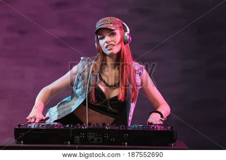 DJ mixing music on color background