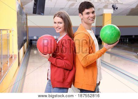 Young man and woman having fun at bowling club