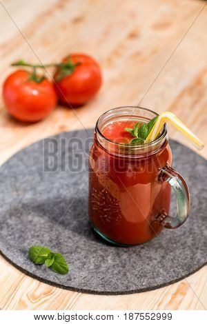Close Up View Of Fresh Tomato Smoothie With Basil Leaves And Straw On Tabletop