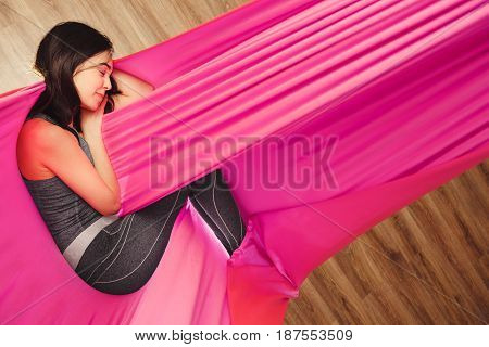 Girl dreaming and meditation in pink silk lighted hammock hanging in relaxed position. Antigravity yoga training in bright gym studio. Aero yoga trainer does exercises