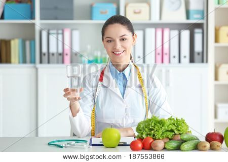 Young female nutritionist holding glass of water while sitting at table in her office