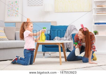 Little girl and her mother playing while cleaning up at home