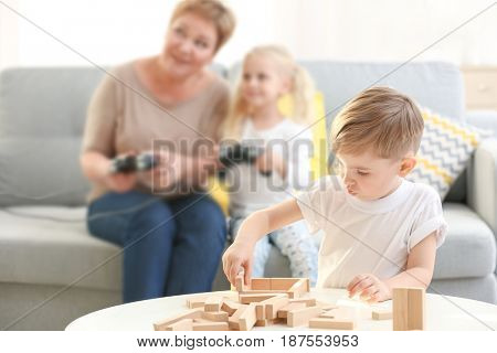 Cute little boy playing with wooden blocks while his sister and grandmother are immersed in video game