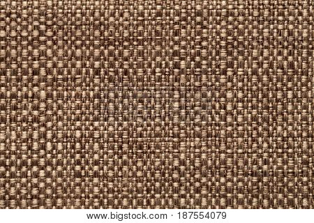 Bronze background with checkered pattern closeup. Structure of the light brown fabric macro.