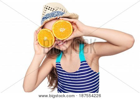 Llittle girl in swimsuit and summer hat having fun with half oranges making fake eyeglasses, over white background