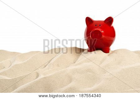 On the Beach - Sand dune with a red  piggy bank in front of a white background - clipping path included