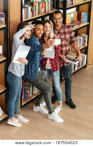 Picture of young happy students standing in library. Looking aside while make selfie by mobile phone.