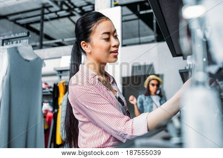 asian hipster girl choosing clothes in shopping mall boutique shopping concept